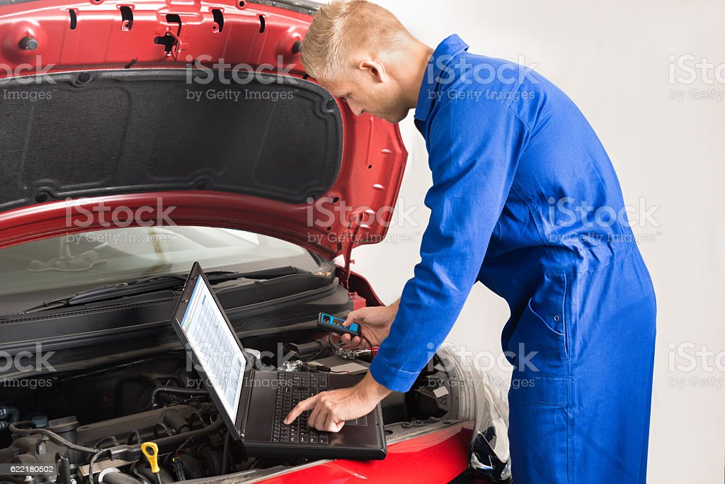 Mechanic Using Laptop While Repairing Car stock photo