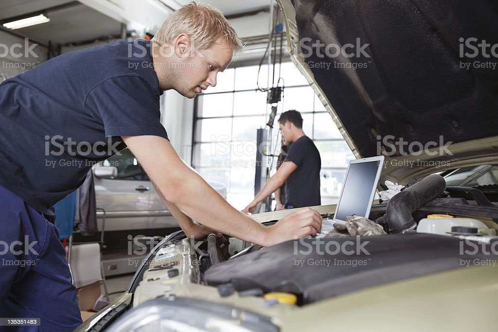 Mechanic using laptop while working on a car under the hood royalty-free stock photo
