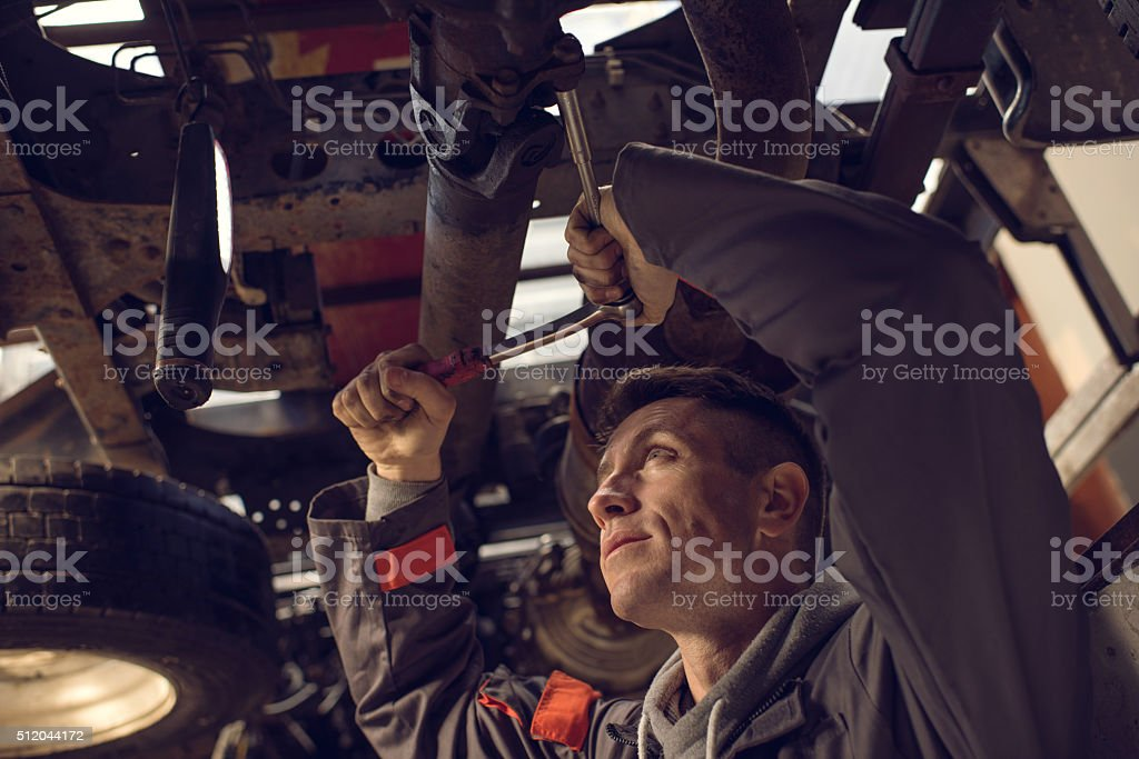 Mechanic using socket wrench while working on a chassis. stock photo
