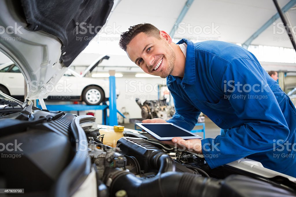 Mechanic using tablet on car stock photo