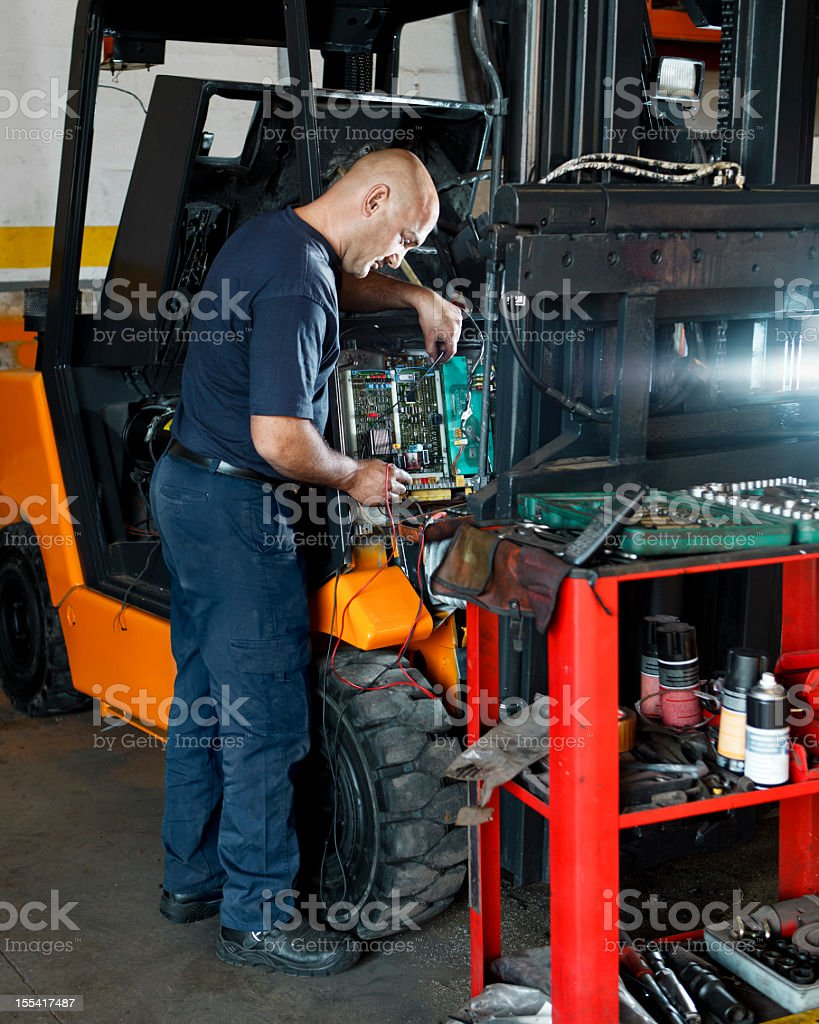 A mechanic using tools to fix a vehicle stock photo