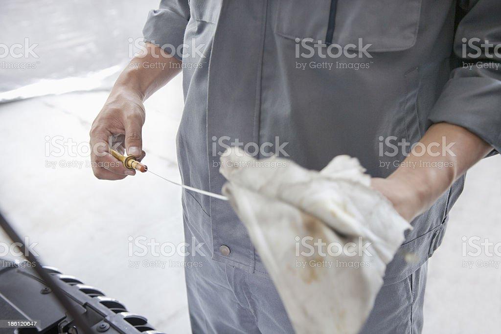 Mechanic Wiping Down Dipstick royalty-free stock photo