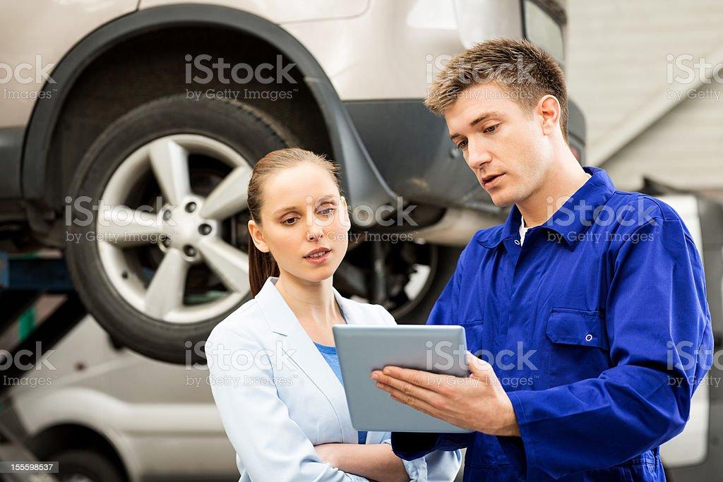 Mechanic With Customer Using Digital Tablet stock photo
