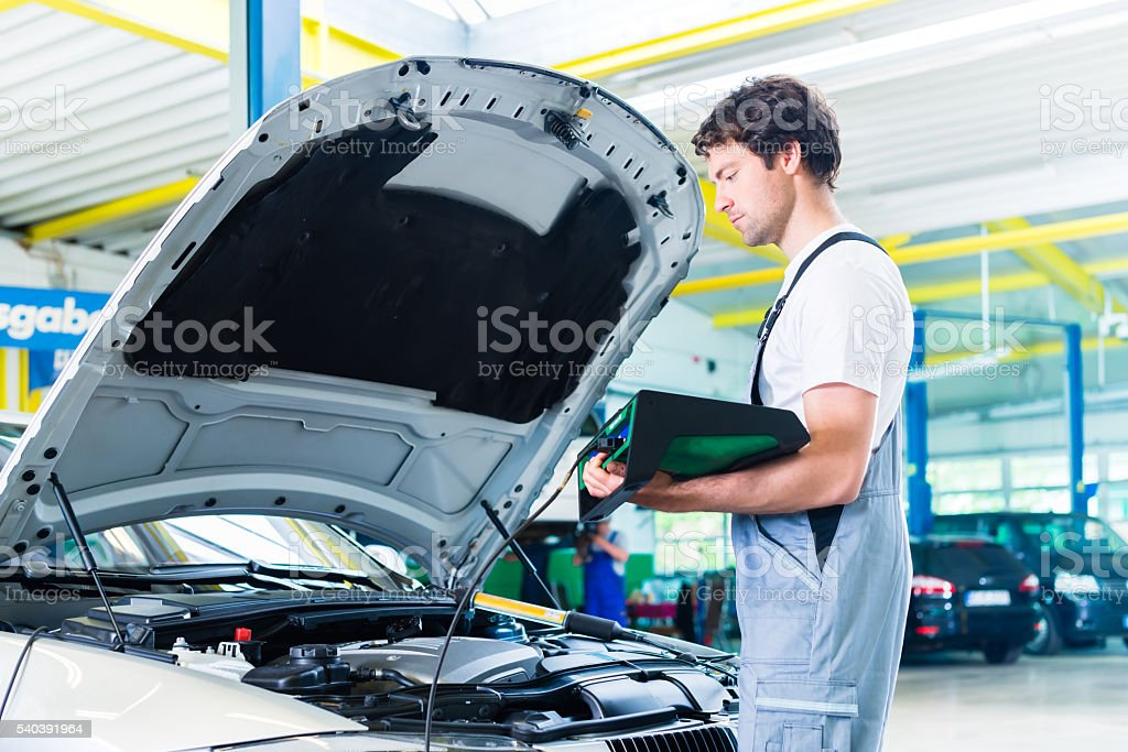 Mechanic with diagnostic tool in car workshop stock photo