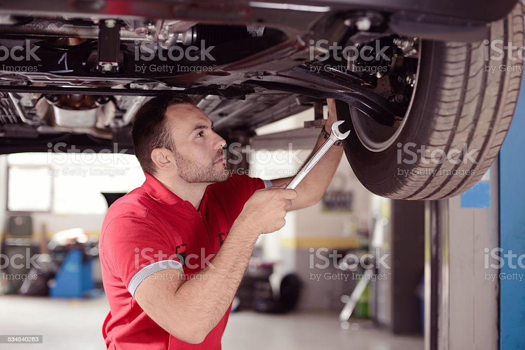 mechanic with tool checking the car stock photo