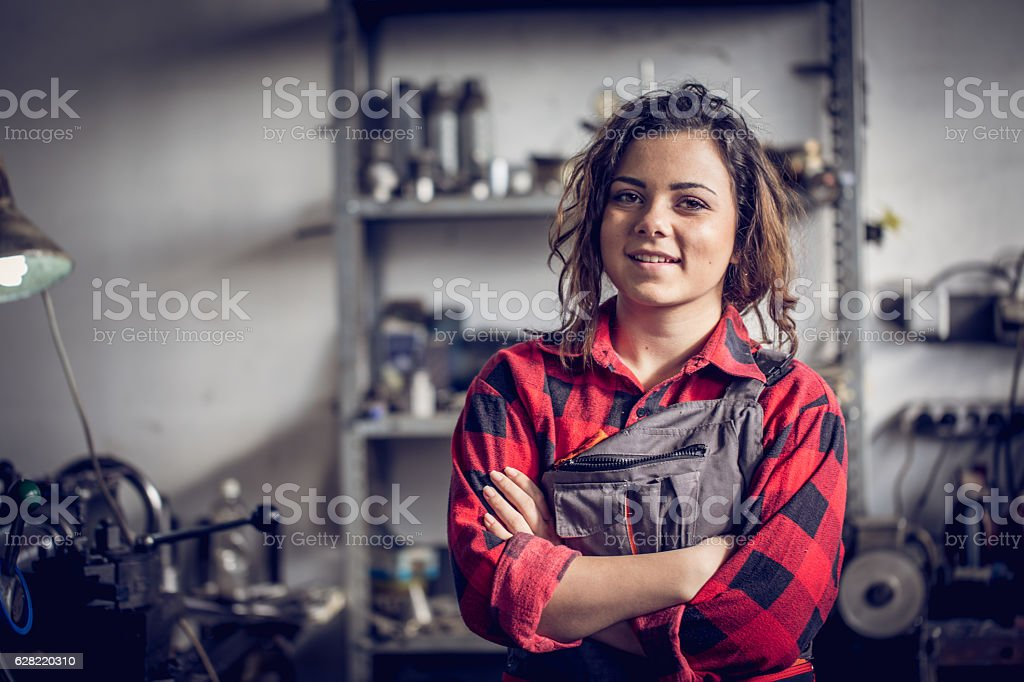 Young cute woman mechanic in her workshop.
