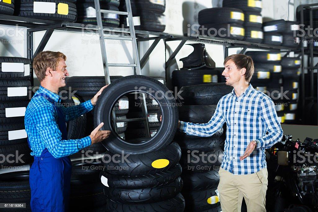 Mechanic working and taking to customer stock photo