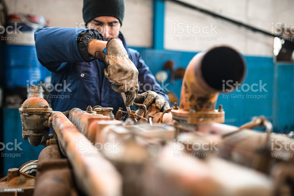 mechanic working in a workshop on a truck engine stock photo