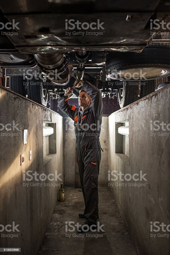 Mechanic working on a chassis of a truck. stock photo