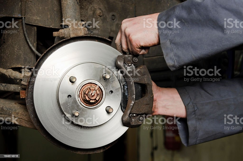 Mechanic working on a new set of brakes stock photo