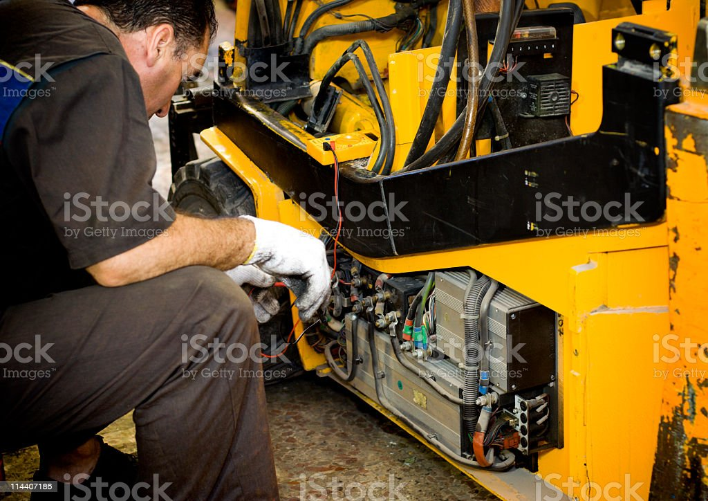 Mechanic working on a yellow machine stock photo