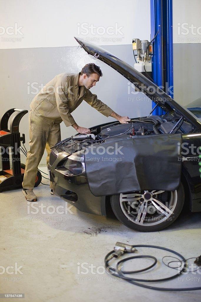 Mechanic working on car engine in garage stock photo