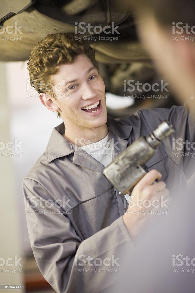 Mechanic working on car in garage stock photo