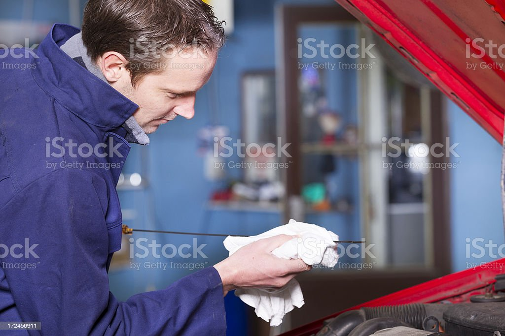 Mechanic working on car, oil level royalty-free stock photo