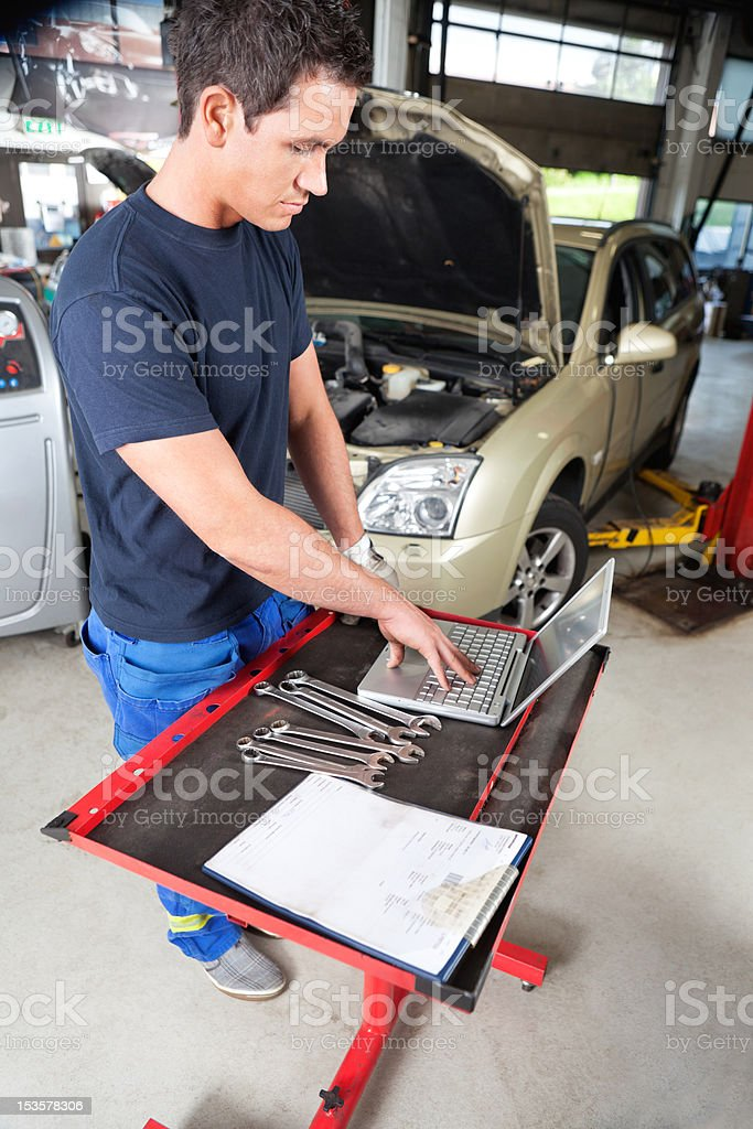 Mechanic working on laptop royalty-free stock photo