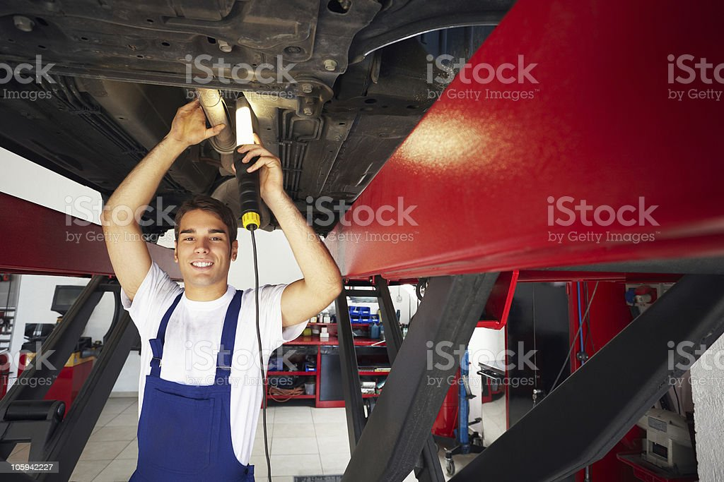 A mechanic working under a car royalty-free stock photo
