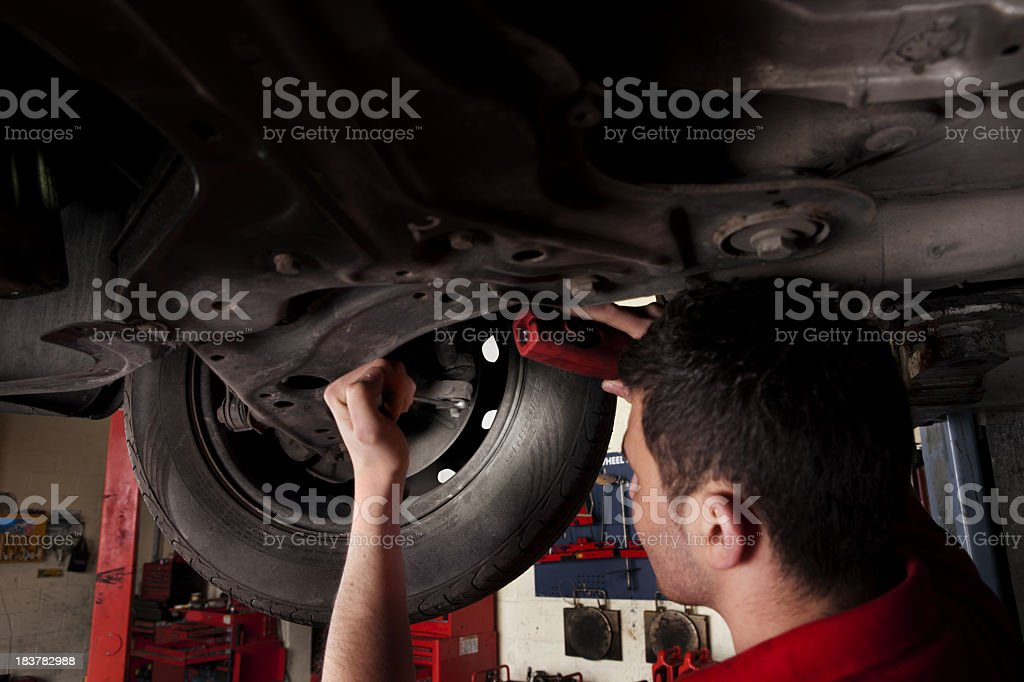 Mechanic working under an elevated car stock photo