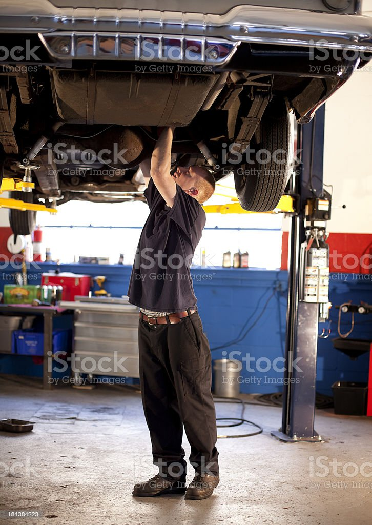 A mechanic works on a car on a lift against the blue wall. stock photo