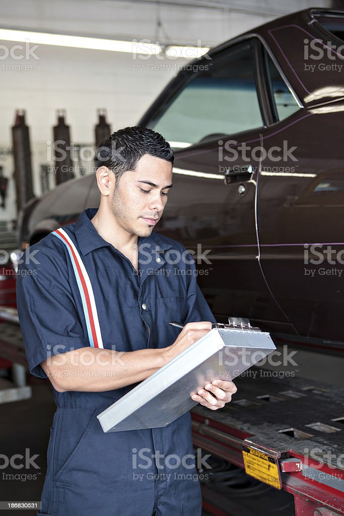 Mechanic writing up a reciept for customer stock photo