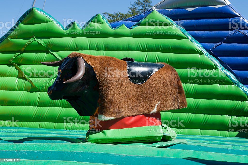 Mechanical bull game surrounded by inflatables stock photo