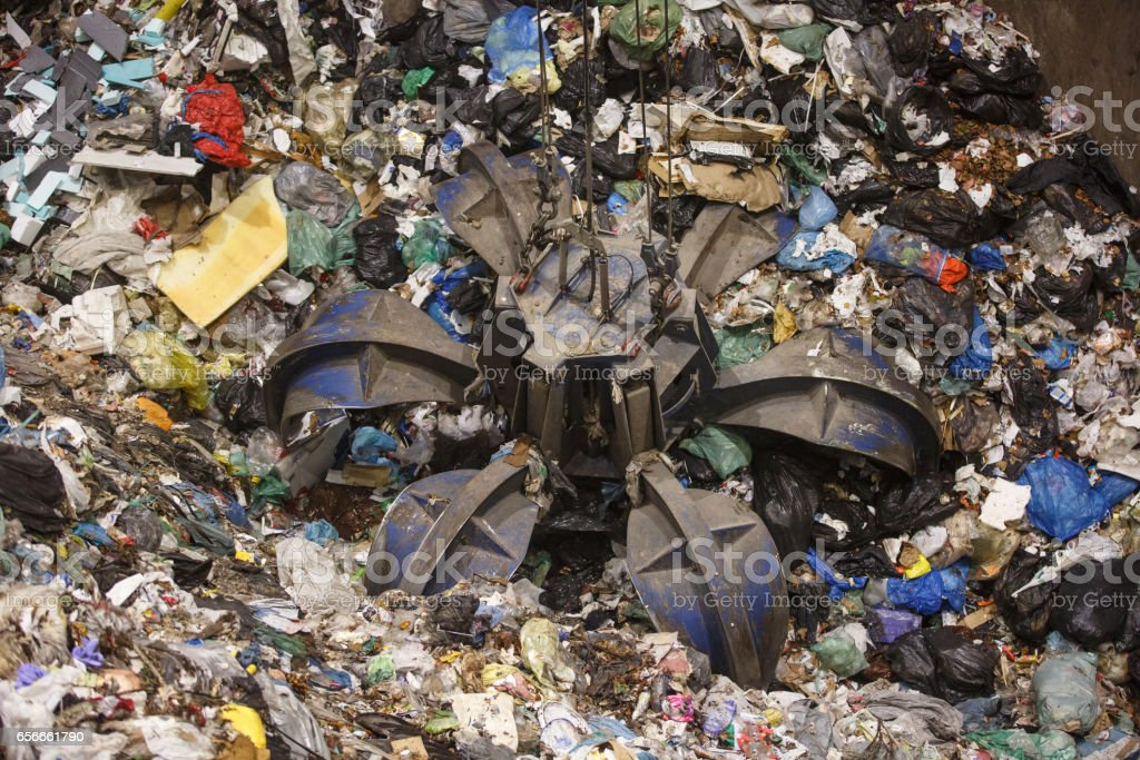 Mechanical claw hand grabbing pile of mixed waste stock photo