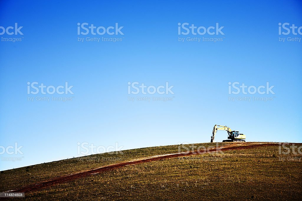 Mechanical digger on top of hill royalty-free stock photo