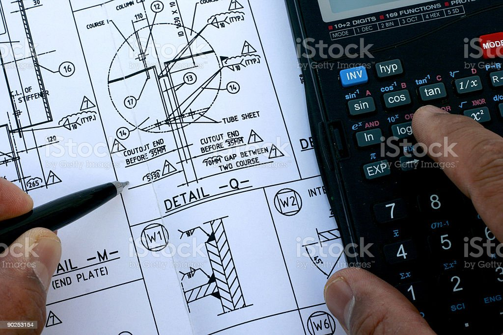Mechanical engineer completing sketch with calculator royalty-free stock photo
