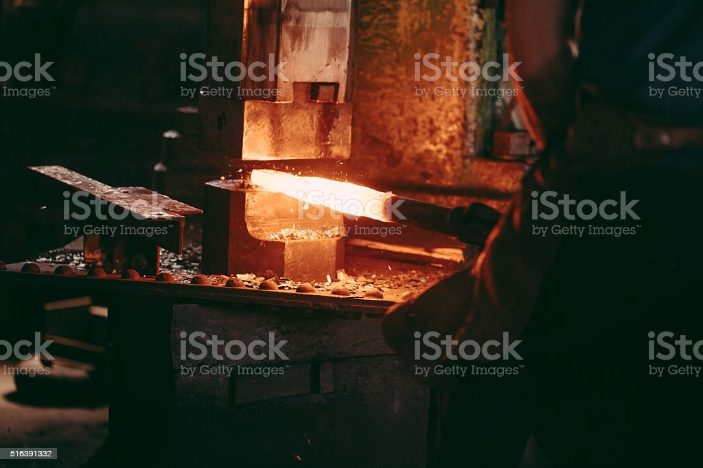 Mechanical hammering of glowing iron in blacksmith forge stock photo