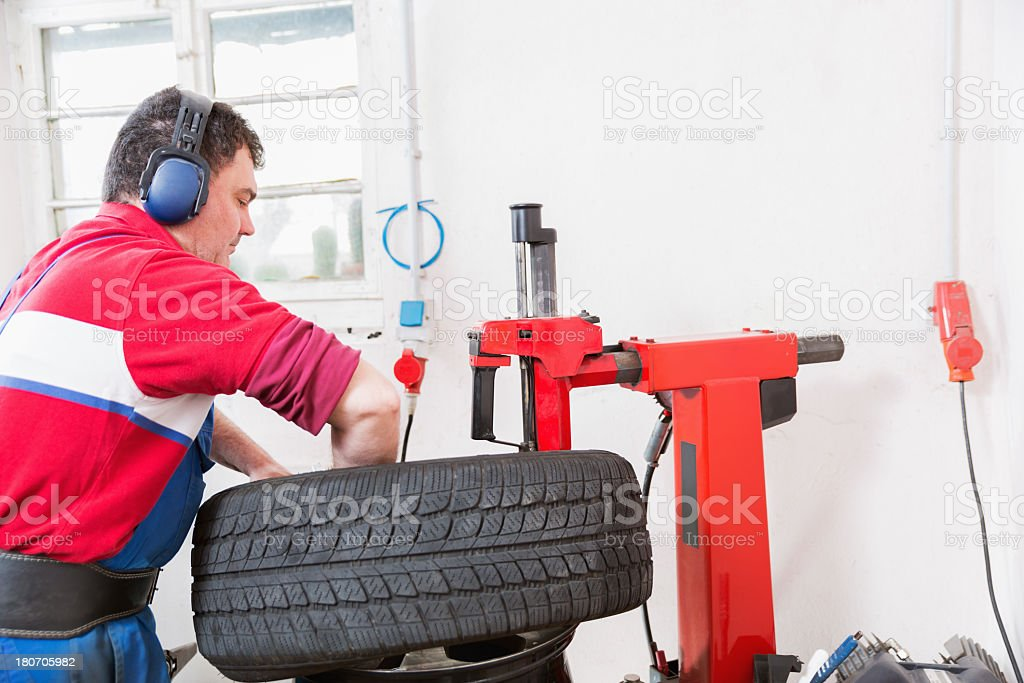 Mechanical repairs a tire in the garage royalty-free stock photo
