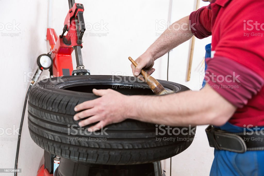 Mechanical repairs a tire in the garage stock photo