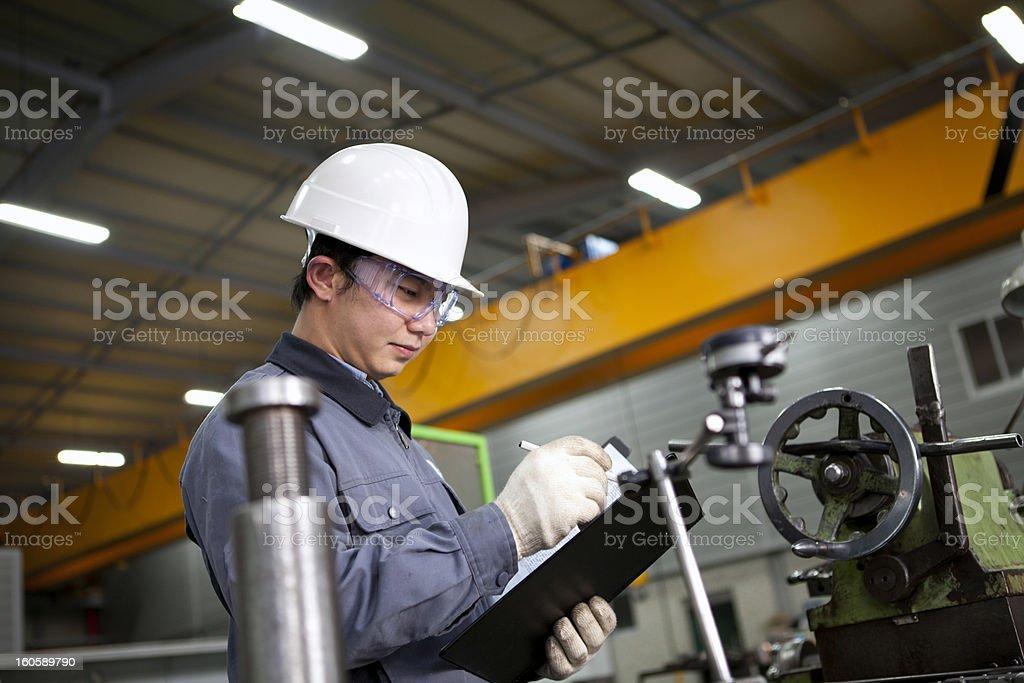 mechanical technician writing on notepad stock photo