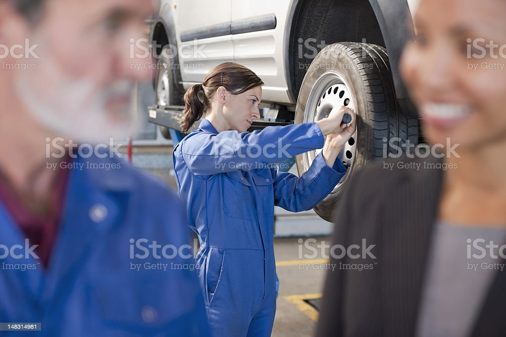 Mechanics and customer in auto repair shop royalty-free stock photo