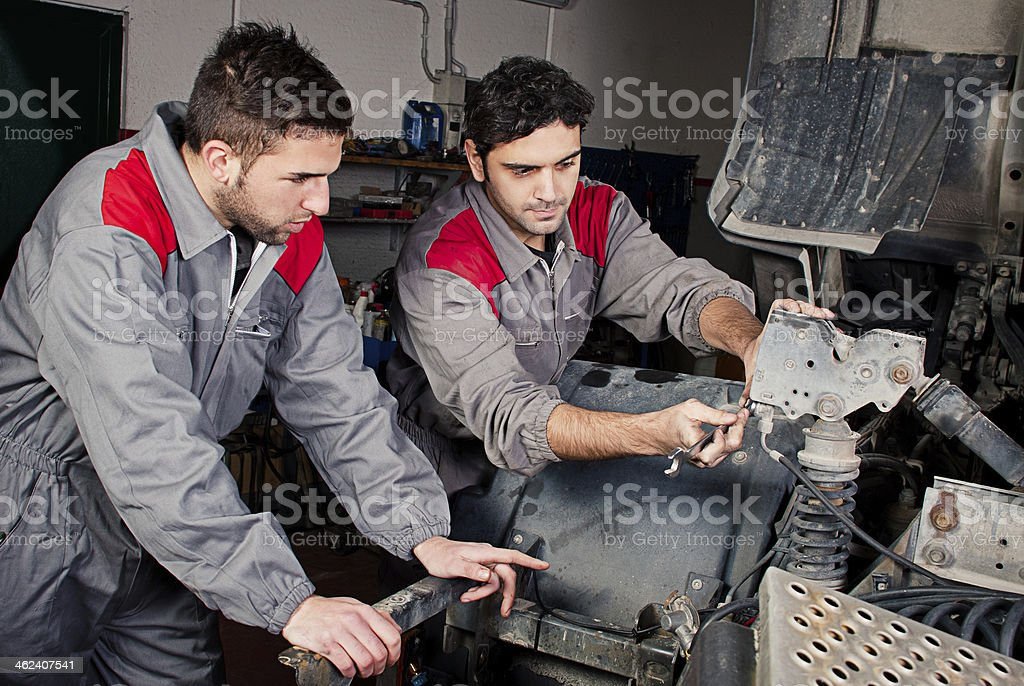 Mechanics at work on a truck. stock photo