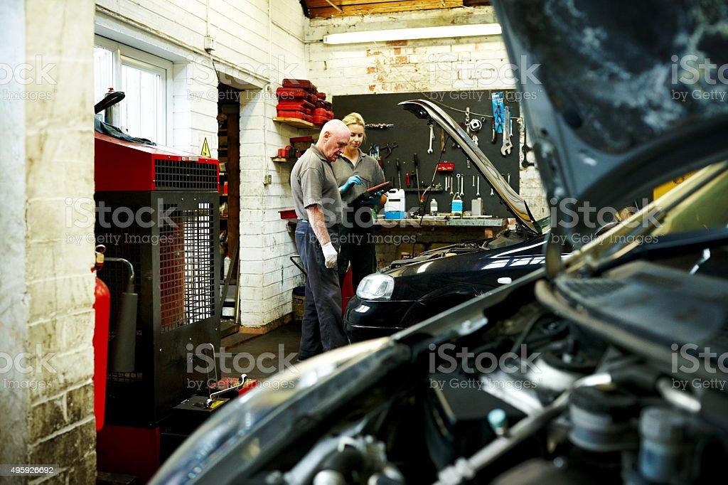 Mechanics checking car after repair stock photo