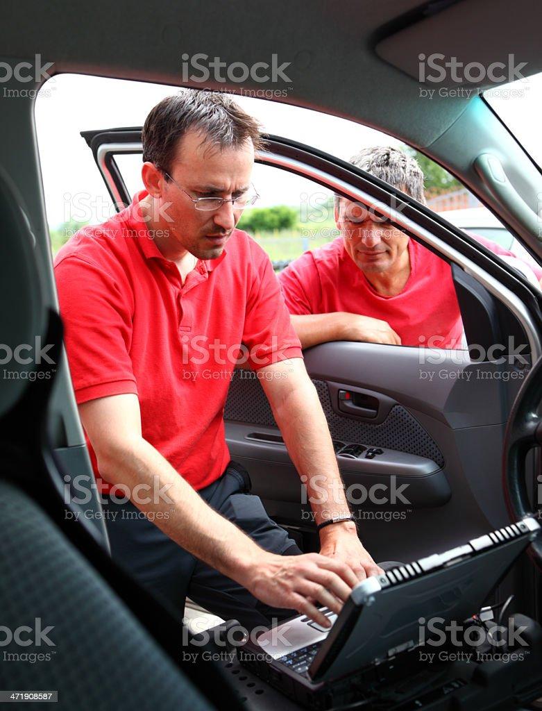 Mechanics ecxamining a vehicle. royalty-free stock photo