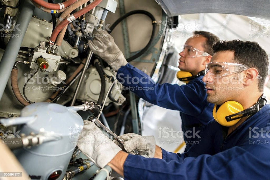 Mechanics fixing a helicopter royalty-free stock photo