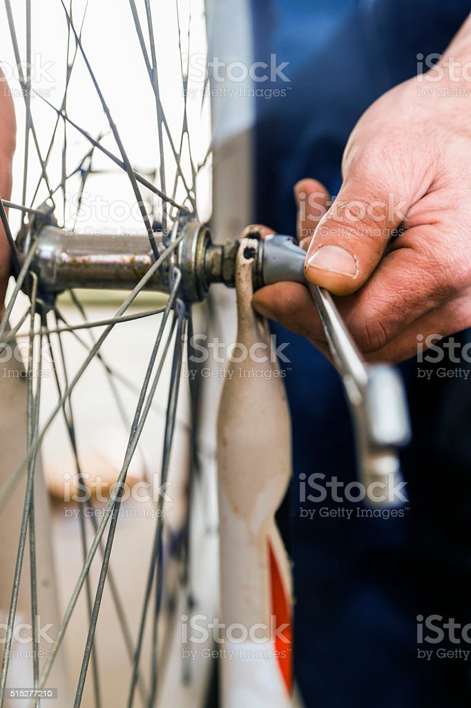 Mechanic's hand fixing nut on bicycle tire stock photo