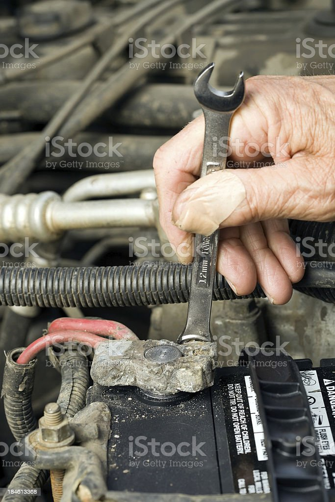 Mechanic's Hand Tightening a Positive Car Battery Connection stock photo