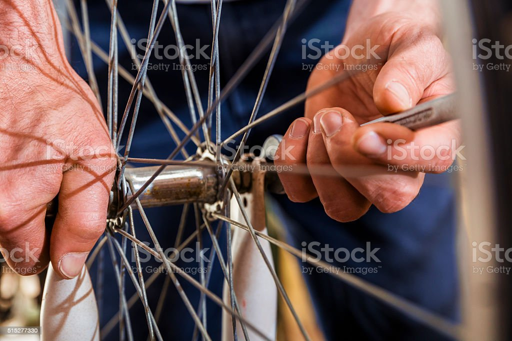 Mechanic's hands fixing bolt on bicycle tire stock photo