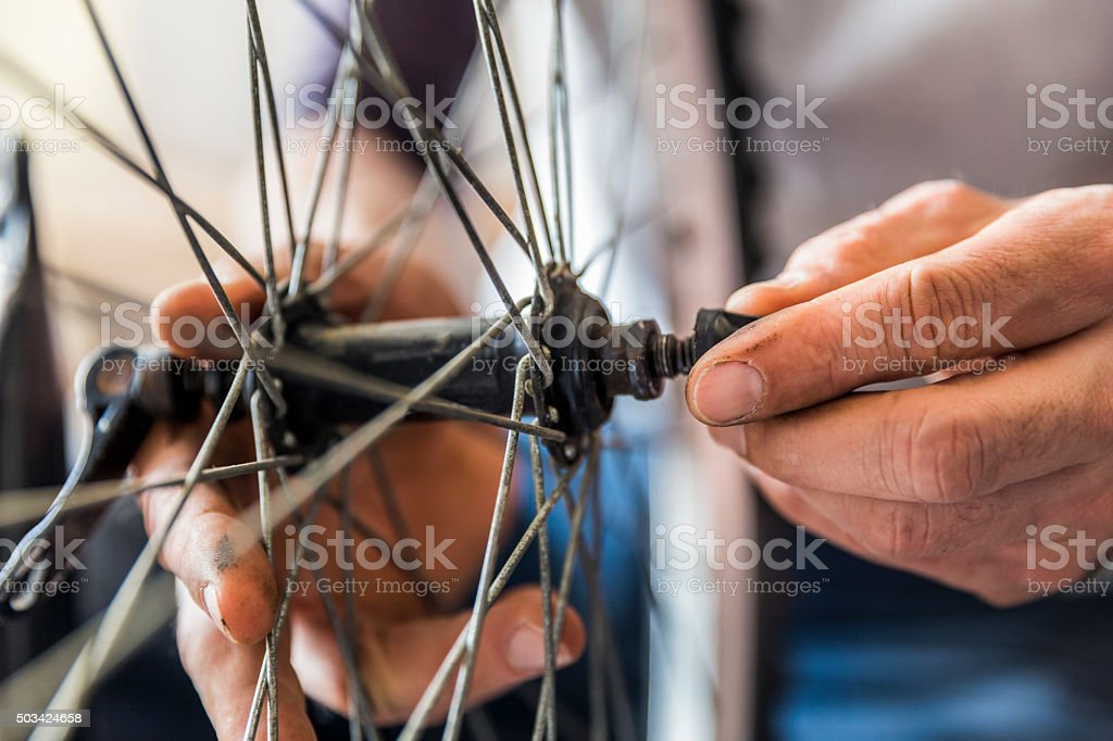 Mechanic's hands fixing nut on bicycle tire stock photo