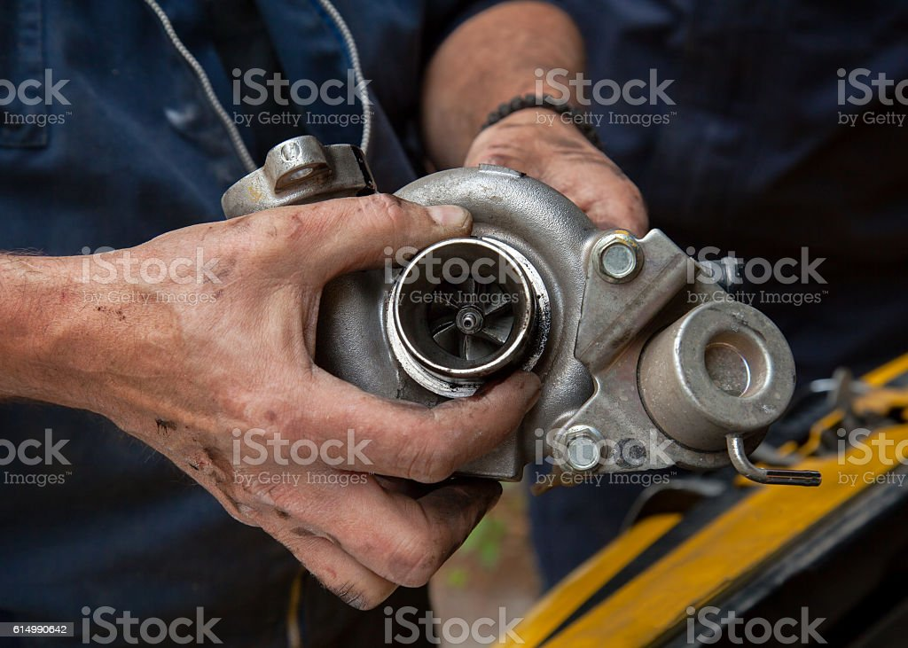 mechanics hold the turbine of a car motor stock photo