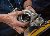 mechanics hold the turbine of a car motor