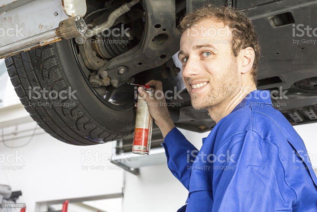 Mechanics repairing a car on hydraulic ramp royalty-free stock photo