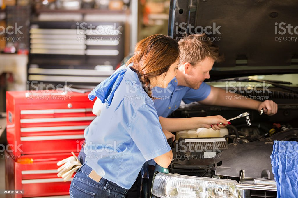 Mechanics work in an automobile repair shop. Man, woman working. stock photo