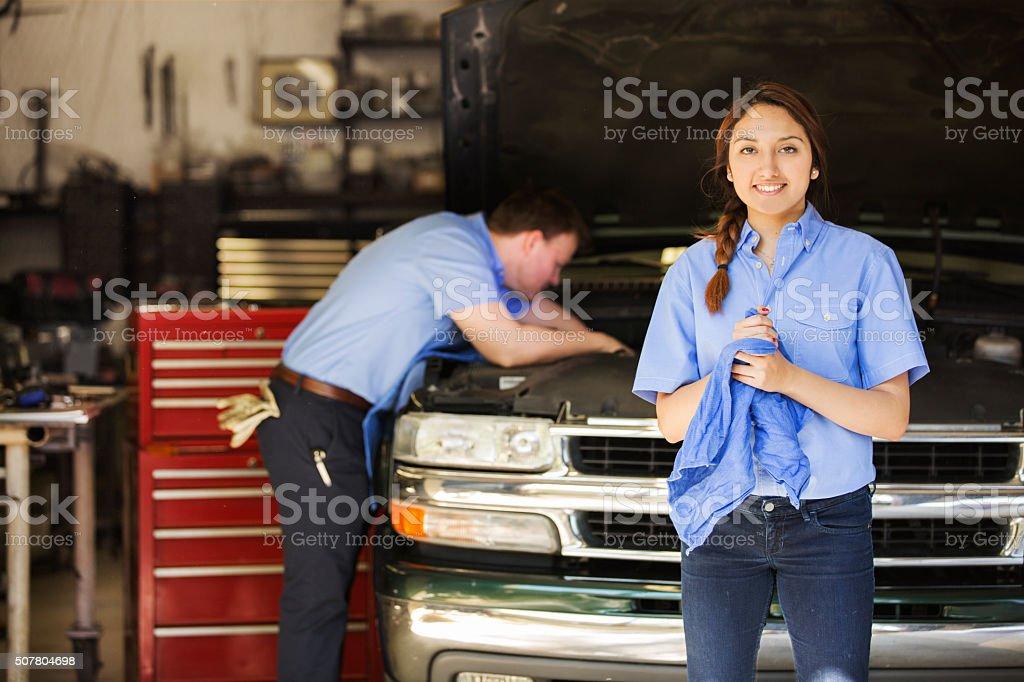 Mechanics work in an automobile repair shop. Man, woman working. stock photo