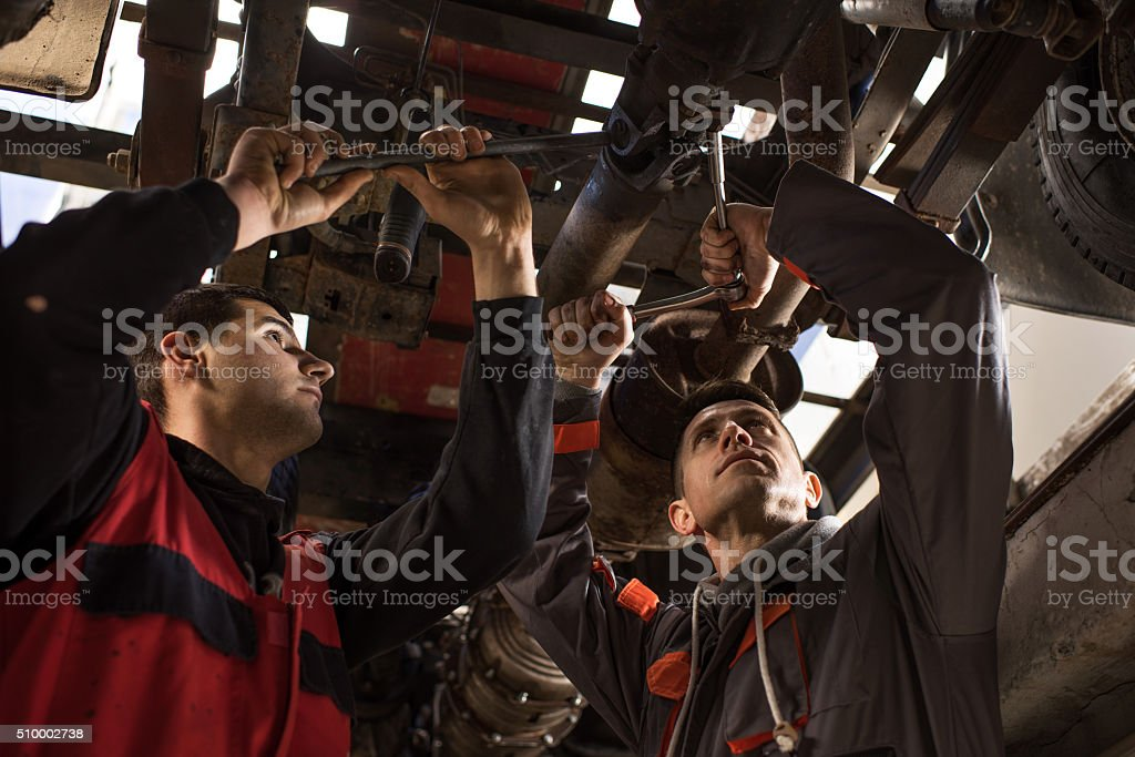 Mechanics working on a bottom part of a car. stock photo