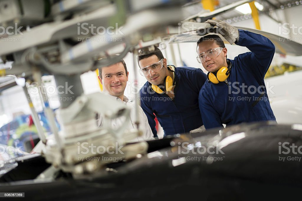 Mechanics working on a helicopter stock photo