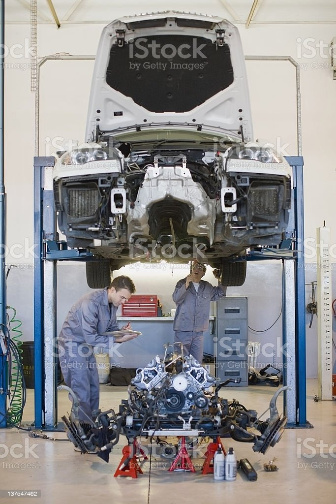 Mechanics working on car in garage stock photo