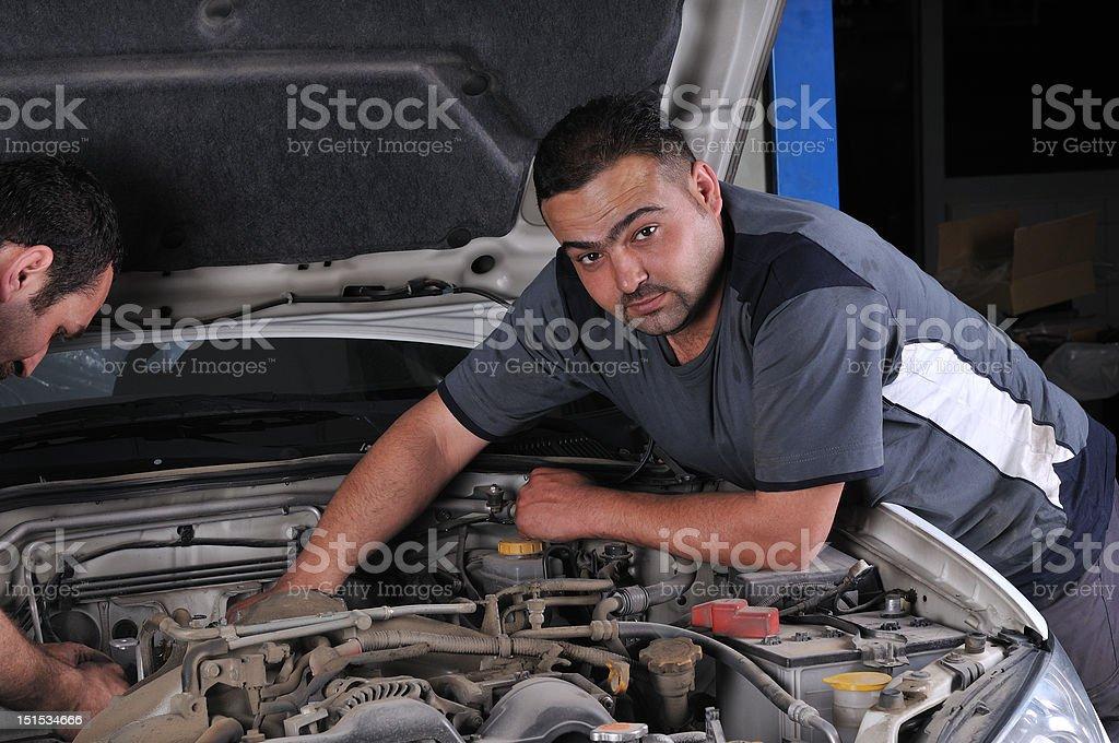 Mechanics working on engine royalty-free stock photo