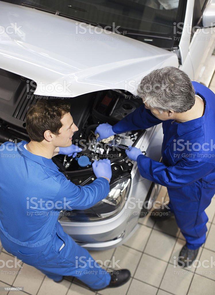 Mechanics working on engine under car hood in auto repair shop royalty-free stock photo